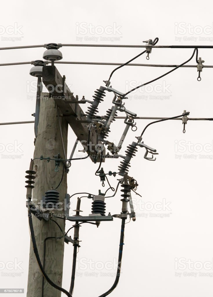 Three circuit breakers on a power pole, one of them has been tripped....