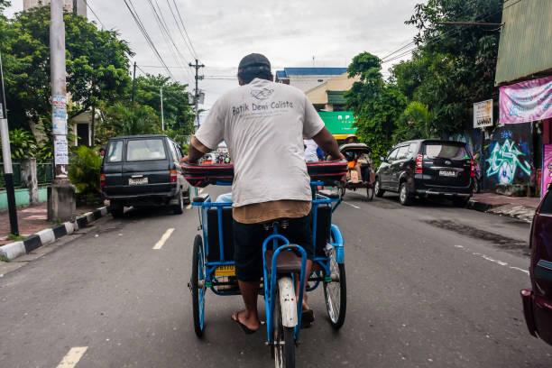 A trishaw at job on the street of Yogyakarta stock photo