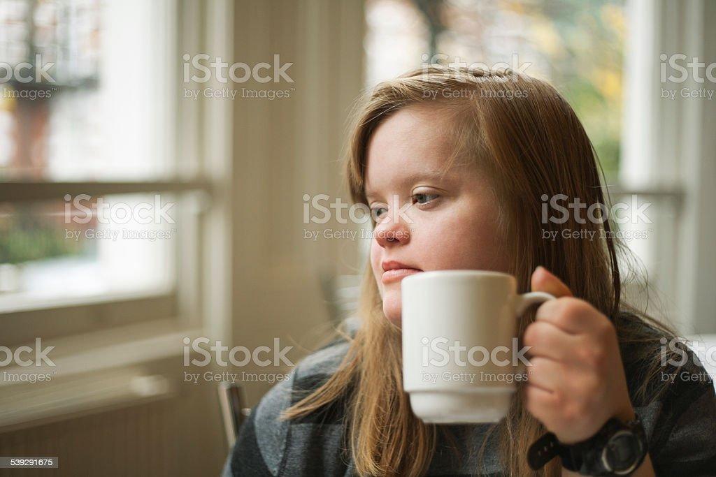 Trisomique, jeune fille, petit déjeuner, boire stock photo