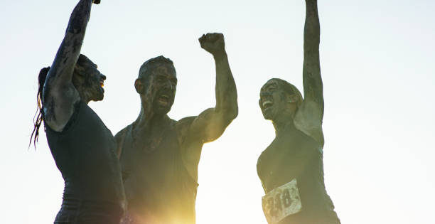 Triumph Three people have just finished a charity mud run together. They stand with their arms up, cheering with the bright summer sun behind them. They are covered in mud and wearing racing numbers. mud run stock pictures, royalty-free photos & images