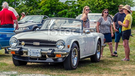 Chester, Nova Scotia, Canada -  August 4, 2018: 1976 Triumph TR6 sports car is being displayed at the annual Graves Island Car Show, Graves Island Provincial Park, Chester, Nova Scotia. People stand, chat and admire the classic cars being shown by their owners.