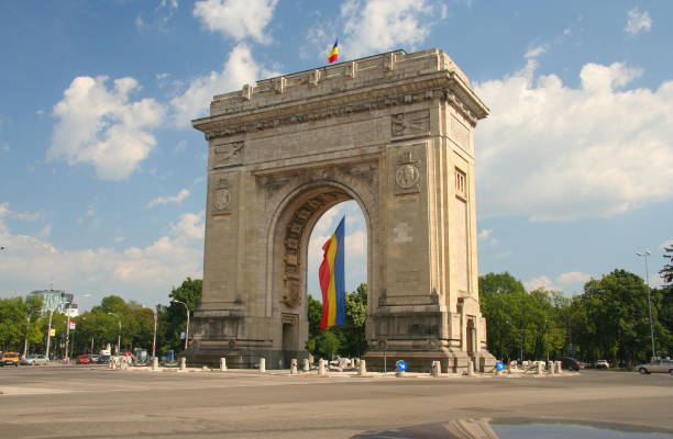 triumphal arch with flag - romania foto e immagini stock
