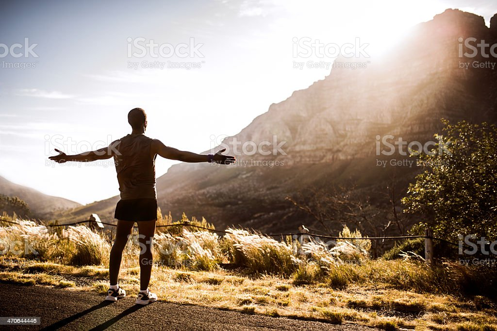 Triumphant African American athlete enjoying fitness in nature stock photo