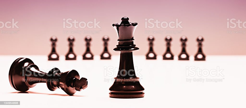 Triumphant chess queen conquers fallen king royalty-free stock photo