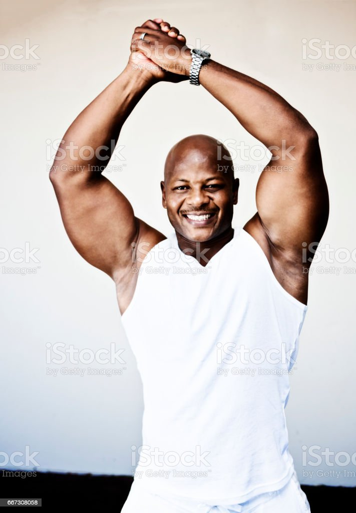 Triumphant well-muscled bodybuilder smiles, clasping hands  in triumph stock photo