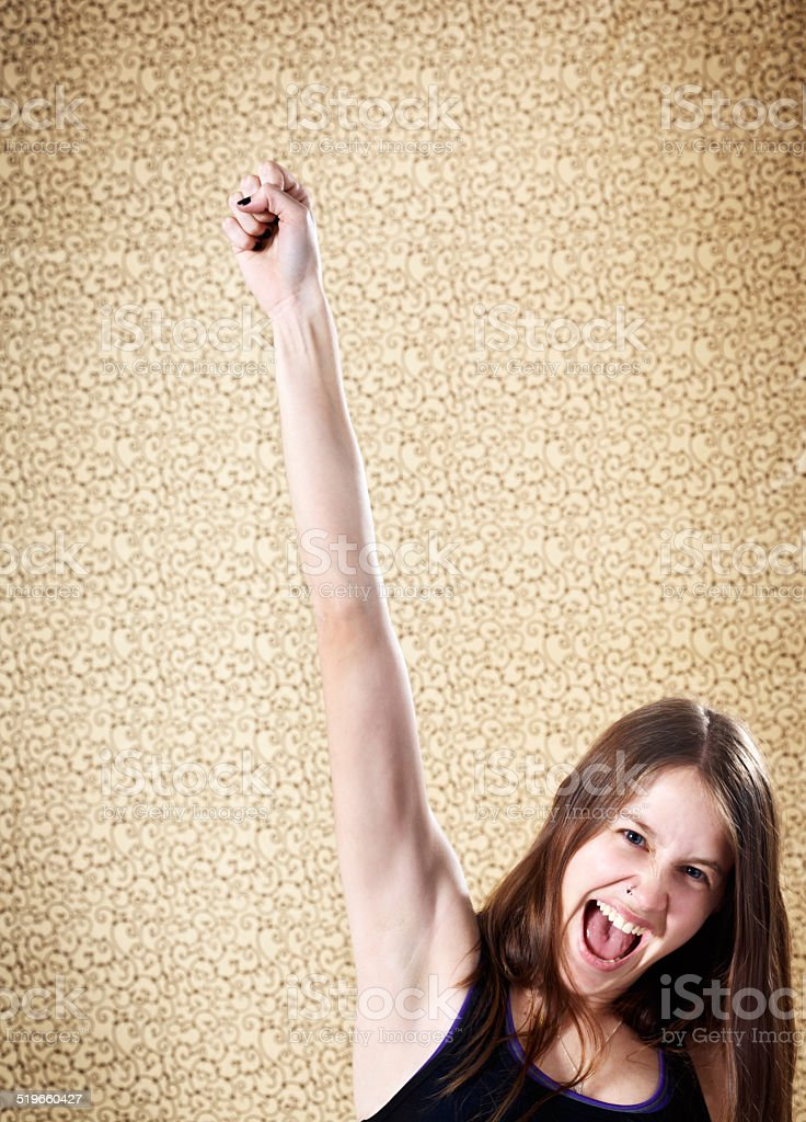 Triumphant young beauty punches the air with energy and enthusiasm stock photo