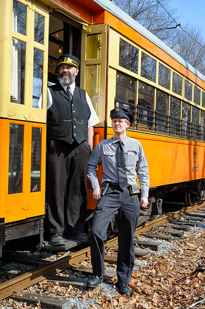 trolley motormen at the door, old fashioned mass transit - transport conductor stock photos and pictures