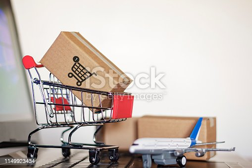 Trolley with cartons and airplane on computer. Online Shopping and International shipping concept