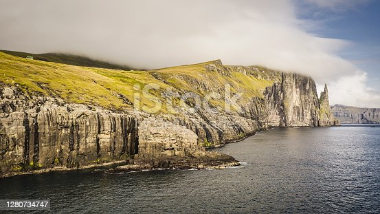 Faroe Islands Trollkonufingur Sea Stack Rock - Monolith, also called 'The Troll Woman's Finger' on the island of Vagar. Vágar Island South-East Coast Trøllkonufingur - 313m tall Monolith - on the right of the summer coastline panorama. East Coast Fjord of Sandavagur village, Vágar Island, Faroe Islands, Kingdom of Denmark, Nordic Countries, Scandinavia, Europe
