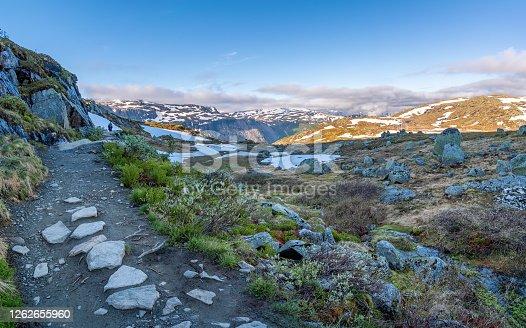Trolltunga, Odda, Norway; July 16, 2020 - Young adult admiring the view from Trolltunga.