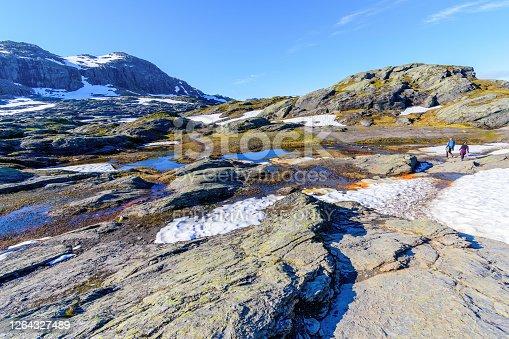 Trolltunga, Odda, Norway; July 16, 2020 - Young adults walking towards Trolltunga