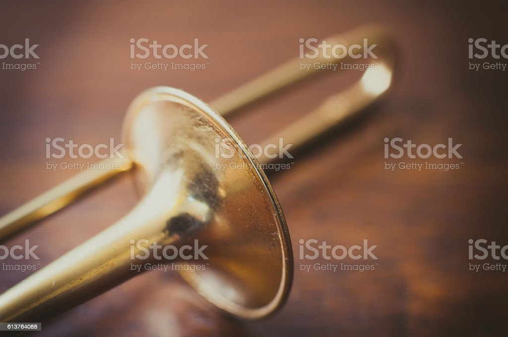 Trombone on wooden floor detail stock photo