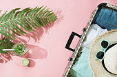 Leaf of fern, tropical detox water and open suitcase with clothes on pastel pink background. Top view with copy space. Summer concept travel.
