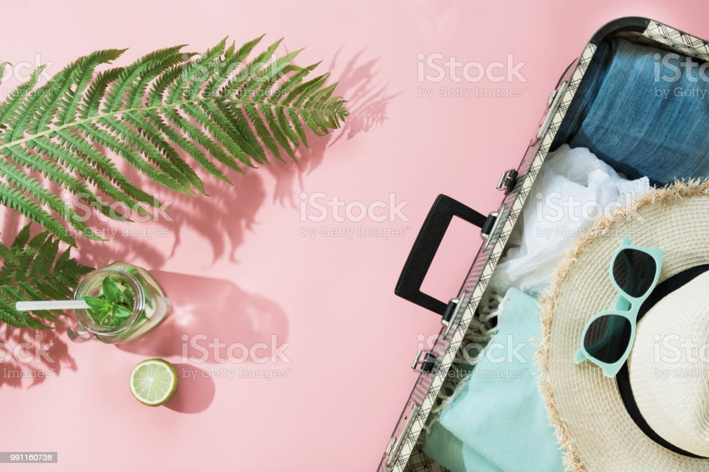 Tropacal summer vacation. Straw beach sunhat, sun glasses, beach towel leaf of fern with shadow on pastel pink background. Top view with copy space. Summer. stock photo