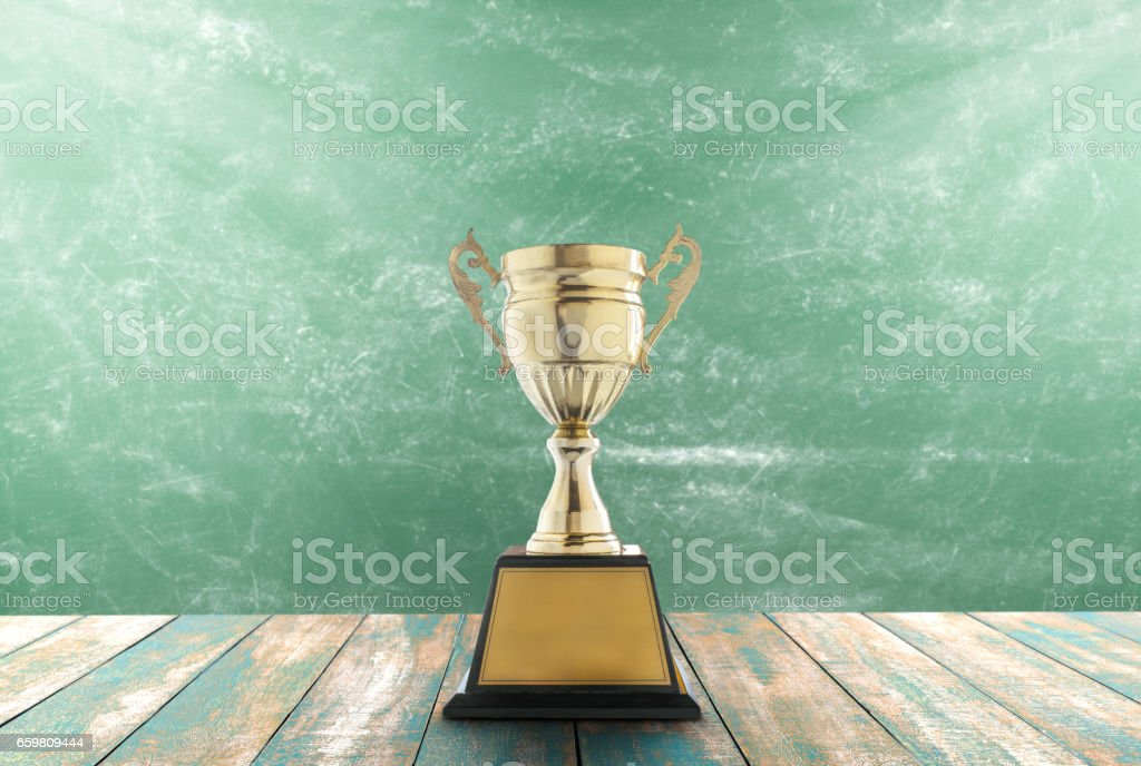 Trophies placed on a wooden table with blackboard background stock photo