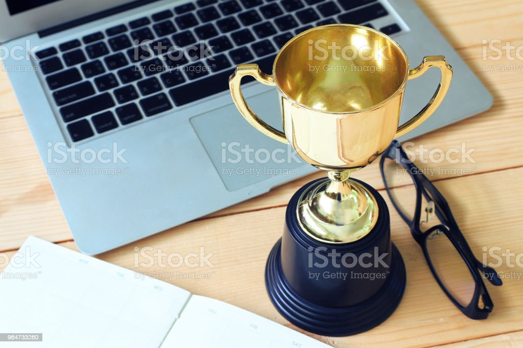 Trophy and laptop and glasses and note book on wood table, win concept. royalty-free stock photo