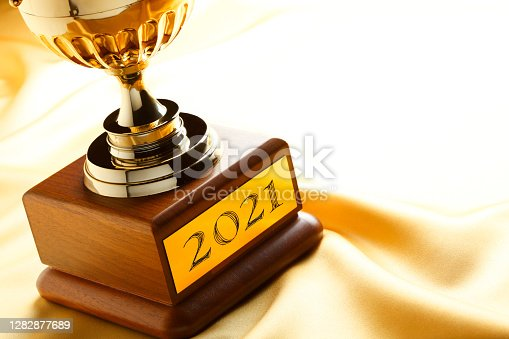 A trophy is engraved with the year 2021 at it is rests on soft golden satin that provides ample room for copy and text.