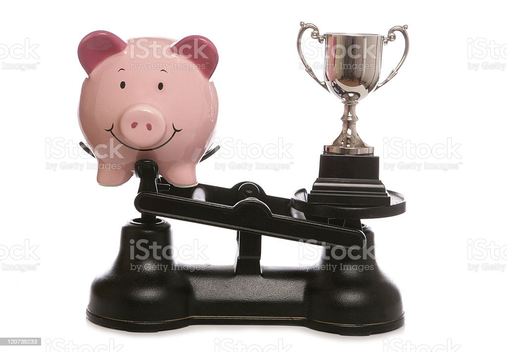 Trophy out weighing piggybank royalty-free stock photo