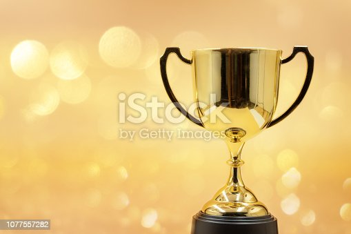 istock trophy over wooden table and dark background bokeh. 1077557282