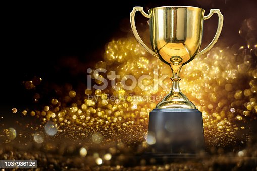 istock trophy over wooden table and dark background 1037936126