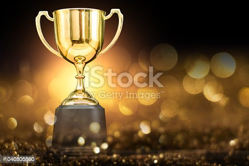trophy over wooden table and dark background