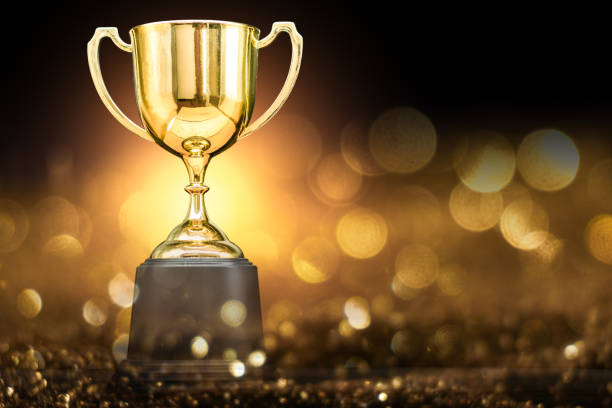 trophy over wooden table and dark background - trophy award stock photos and pictures