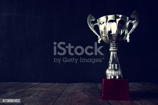 istock trophy over wooden table and dark background 610680452