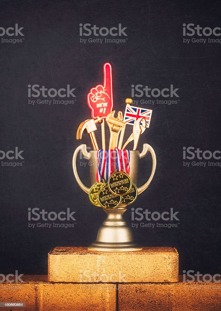 Trophy with winner medals and gold tools on gold bricks stock photo