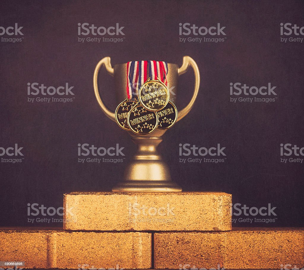Trophy with winner medals on gold colored bricks stock photo