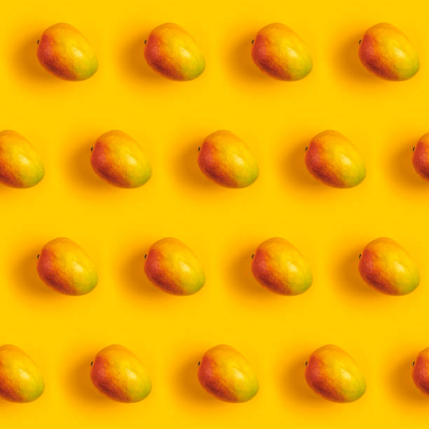 Tropical abstract background. Juicy ripe mango pattern on yellow background top. Seamless pattern with mango. stock photo