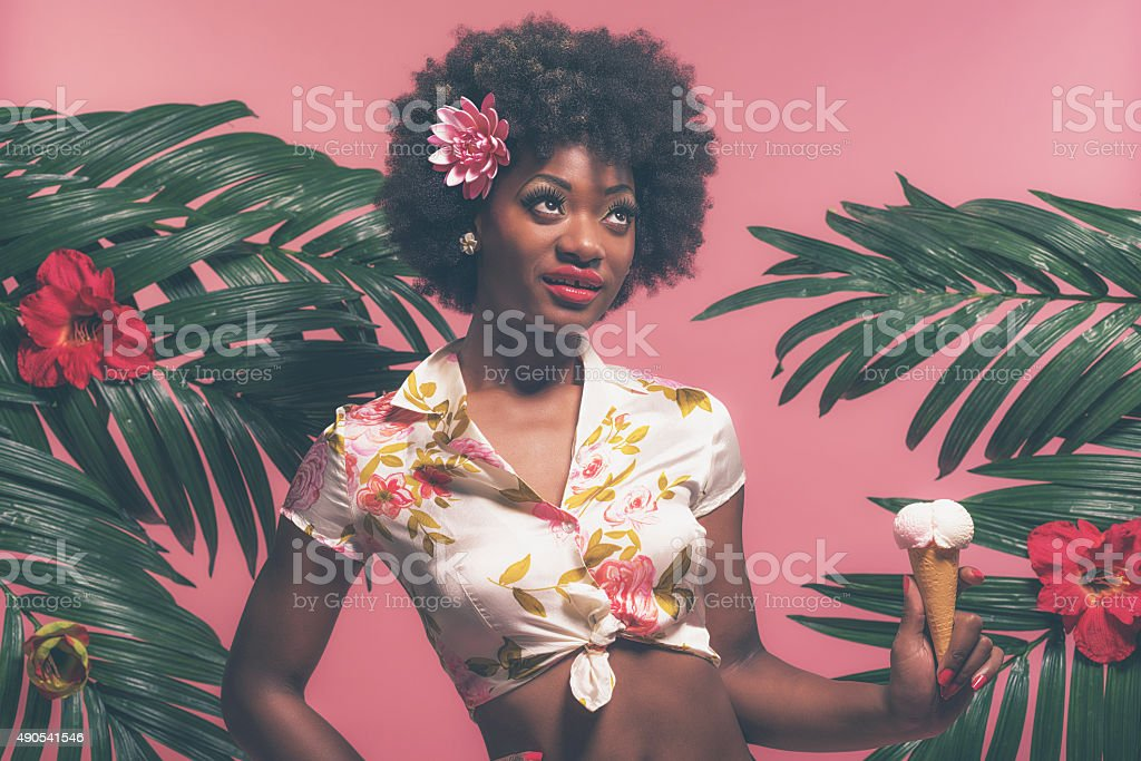 Tropical Afro American Pin-up Holding Ice Cream Standing Between Palms. stock photo