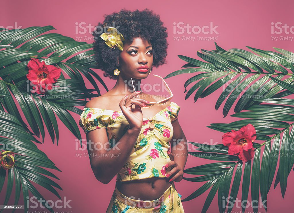 Tropical Afro American Pin-up Holding Sunglasses. Against Pink Background. stock photo