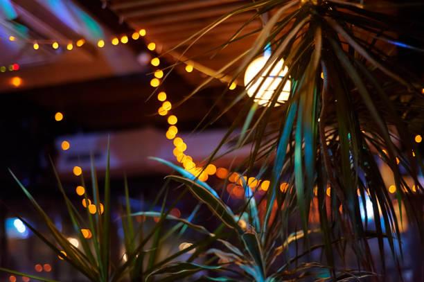 tropical bar athmocphere achtergrond met gele garland bokeh. vakantie nachtleven concept - strandfeest stockfoto's en -beelden