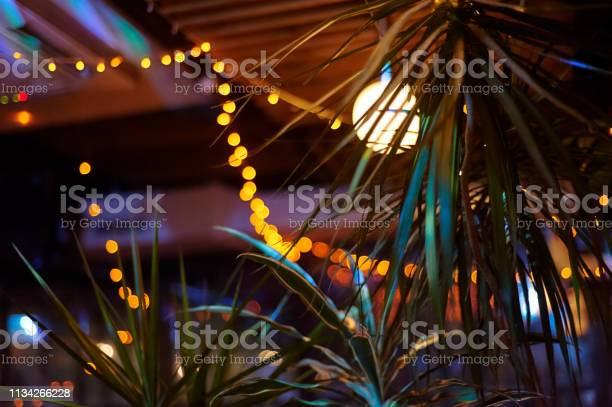Photo of tropical bar athmocphere background with yellow garland bokeh. vacation night life concept