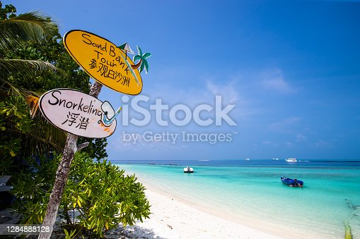 A sign near the beach gives notice to snorkelling and sandbar tours in both the English and Chinese languages