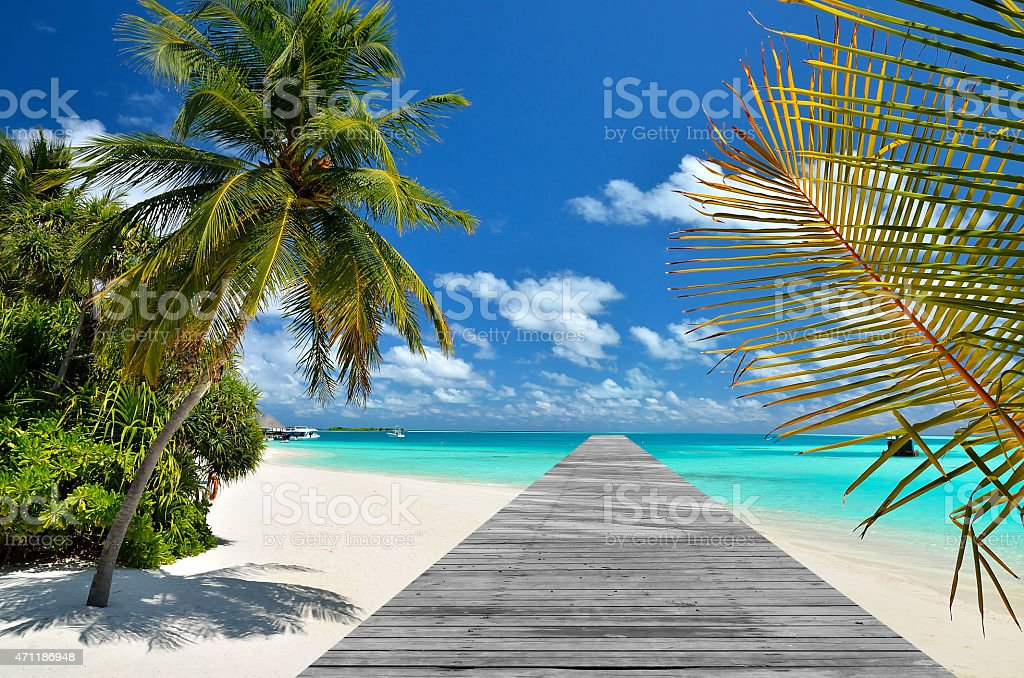 Tropical beach and wooden bridge pier stock photo