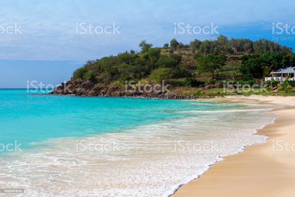 Tropical beach at Antigua island in Caribbean with white sand, turquoise ocean water and blue sky stock photo