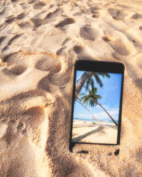Tropical beach image on smartphones screen stock photo