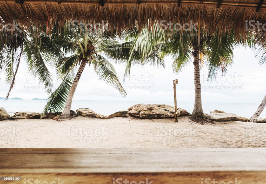 Tropical beach in summer, wood table top with blurred coconut trees, sand and the beach background stock photo