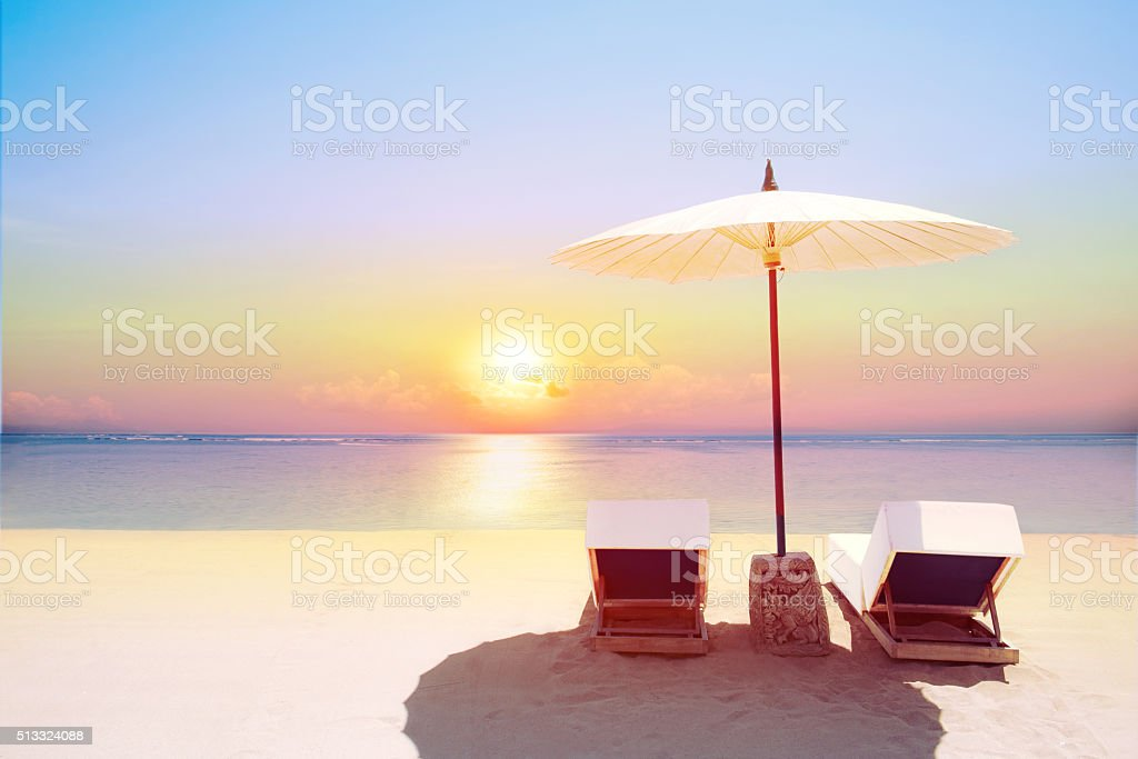 Tropical Beach In Sunset With Beach Chairs And Umbrella Stock Photo