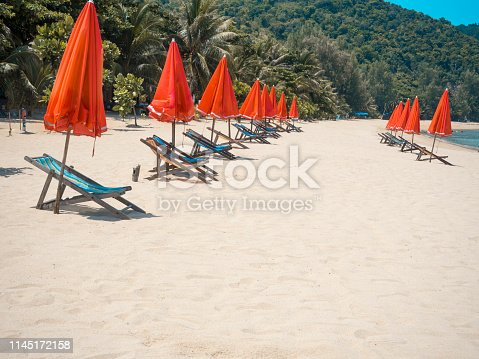 Tropical beach with red parasol