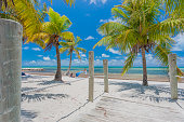 Idillyc tropical beach with white sand an turquoise water and many palm trees in Key West, Florida, USA. Famous travel destination.