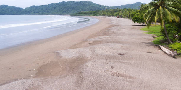tropical beach, Playa Tambor aerial view form a low flying aircraft about to land in a small beach town in Costa Rica nicoya peninsula stock pictures, royalty-free photos & images