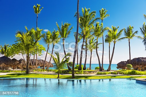 istock Tropical beach resort with lounge chairs and umbrellas 547517756