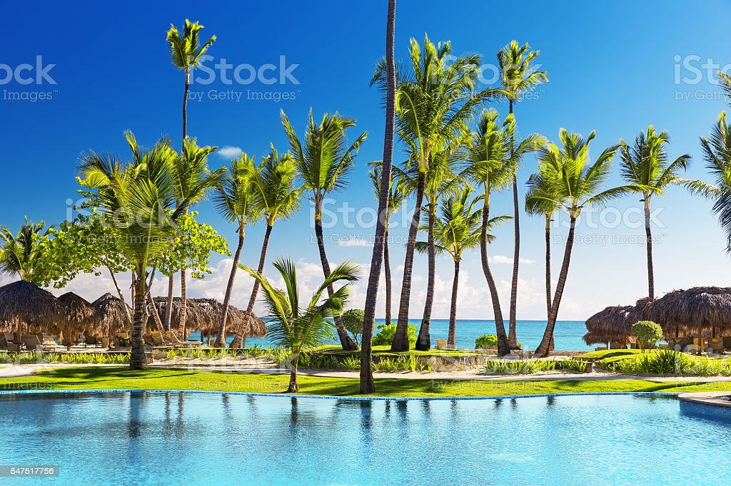Tropical beach resort with lounge chairs and umbrellas stock photo