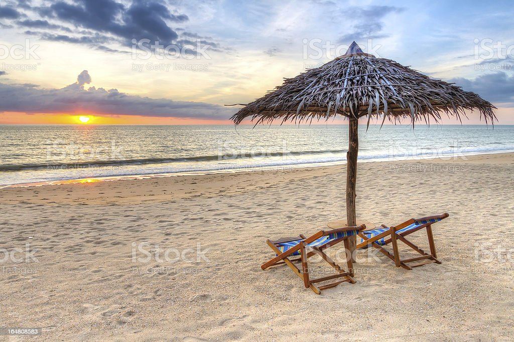 Tropical beach scenery with parasol at sunset stock photo