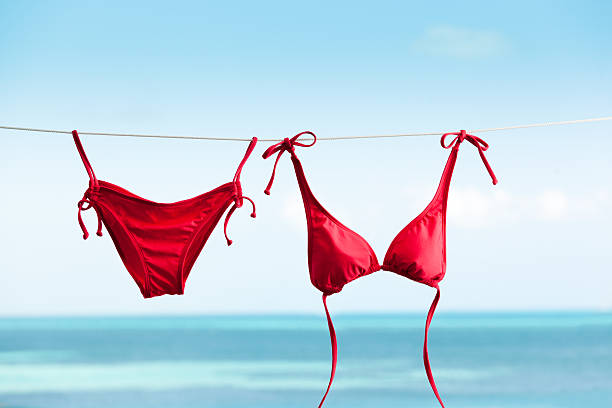 Tropical Beach Vacation with Bikini Swimwear Drying on Clothes Line Subject: Bikini swimwear hanging on clothesline for drying, vacationing on tropical beach holiday. bikini stock pictures, royalty-free photos & images