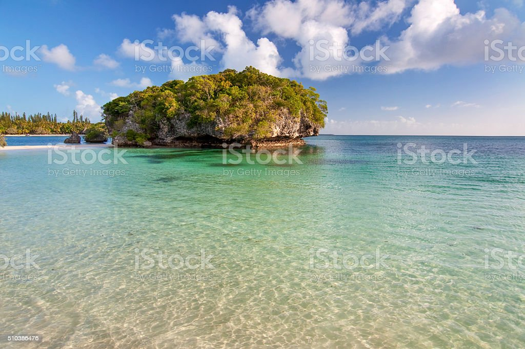 Tropical beach with a rock in the water stock photo