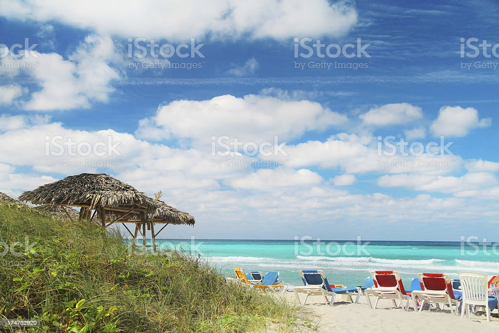 Tropical Beach with chairs and grassy dune. royalty-free stock photo