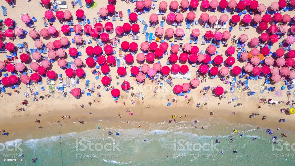 Tropical beach with colorful umbrellas - Top down aerial view stock photo